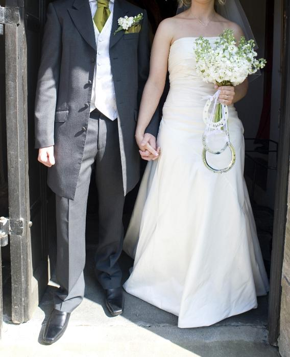 a wedding couple stepping out of the church after the marriage ceremony